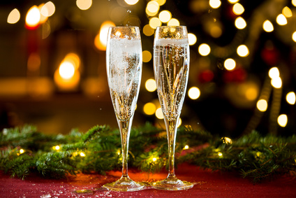 Background of two glasses of champagne, spruce branches on red table cloth. Living room decorated with lights and candles and Christmas tree